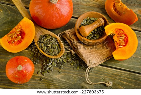 Pumpkins and seeds  on a wooden background. Selective focus - stock photo