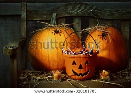 Pumpkins and spiders with candles on bench at night - stock photo