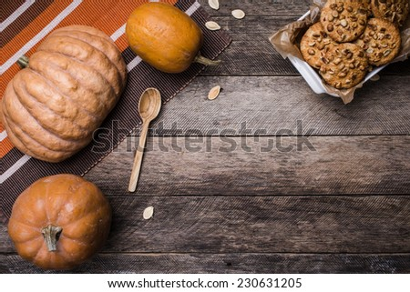 Pumpkins and tasty cookies with nuts on wooden table. Autumn Season food photo - stock photo