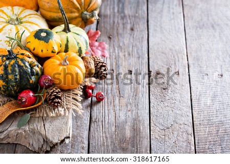 Pumpkins and variety of squash on a rustic table - stock photo