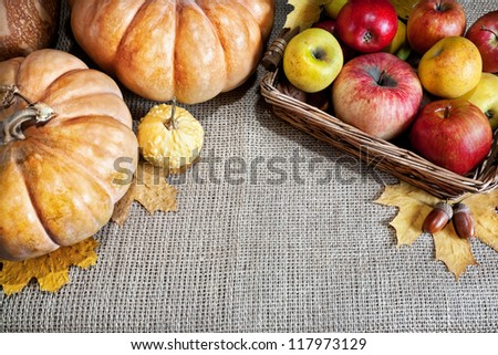 Pumpkins, apples in the basket, acorns and autumn leaves around on textured background. Free space for your text - stock photo
