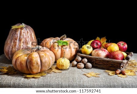 Pumpkins, apples in the basket, nuts, acorns and autumn leaves around on textured cloth at black background. Free space for your text - stock photo
