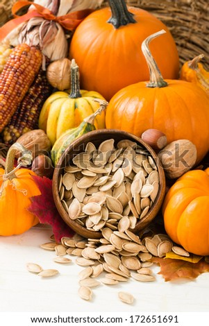 Pumpkins, gourds, nuts and Indian corn, also known as flint corn, surround a wooden bowl overflowing with healthy toasted pumpkin seeds - stock photo