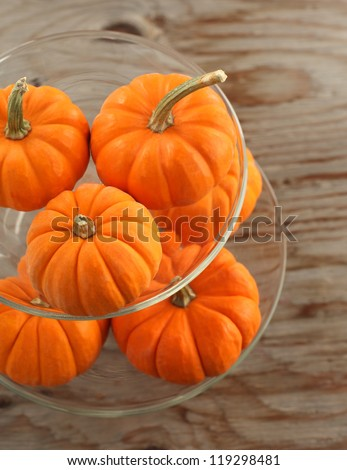 Pumpkins in glass vase on a wooden table