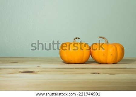 pumpkins on a wooden table over grunge background - stock photo