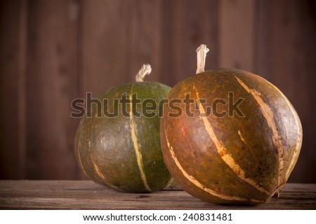 Pumpkins on aged wooden background - stock photo
