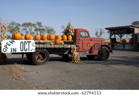 Pumpkins on an old red farm truck with a sign advertising that the farm stand will be open in October. - stock photo