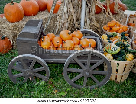 Pumpkins stacked in an old fashioned wheeled carriage surrounded by baskets of other holiday vegetables for Halloween and Thanksgiving. - stock photo