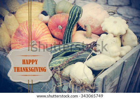 Pumpkins with Happy Thanksgiving paper tag in retro colors - holiday card - stock photo