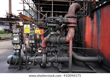 Pumps and pipework on industrial site.