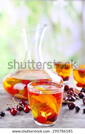 Punch with berries in glassware on wooden table on light blurred background