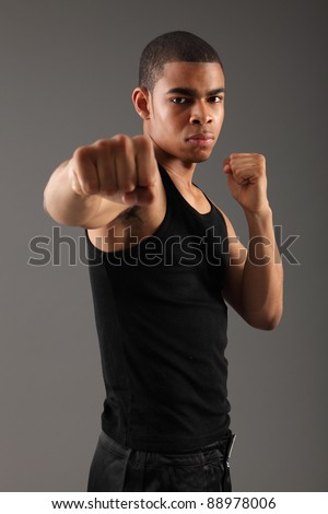 Punch with clenched fist of a handsome young african american man, showing off his muscles and fit physique in an aggressive fight pose wearing black vest, shot against grey background. - stock photo