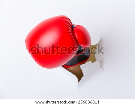 Punching boxing glove though over paper wall - stock photo