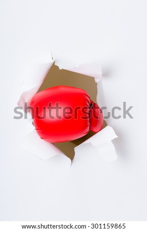 Punching boxing glove though over white paper - stock photo