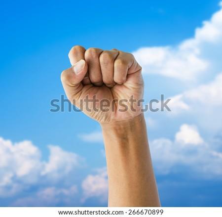 punching fist on blue sky - stock photo
