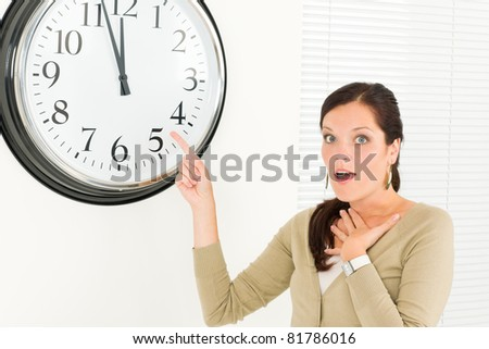 Punctual businesswoman young attractive pointing at clock portrait - stock photo