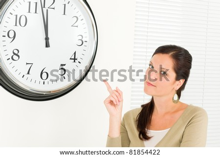 Punctual businesswoman young attractive pointing at clock portrait