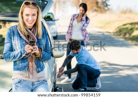 Puncture wheel man changing tire help two female friends - stock photo