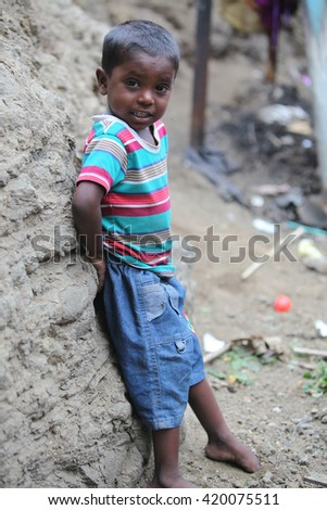 Pune, India - July 16, 2015: A poor Indian boy standing at a construction site where his parents work in India