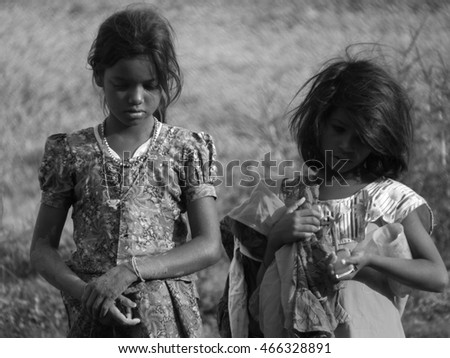 Pune, India - October 30, 2013: Poor Indian girls lost in their thoughts on a hot summer afternoon.