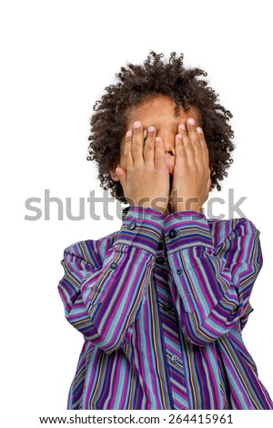 Punished child cries. Resentful boy covered his face with his hands. - stock photo