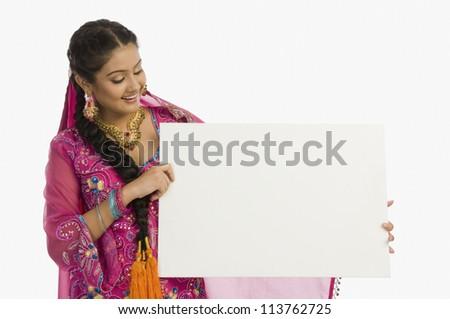 Punjabi woman holding a blank placard and smiling - stock photo