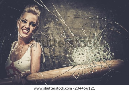 Punk girl breaking glass with a baseball bat - stock photo