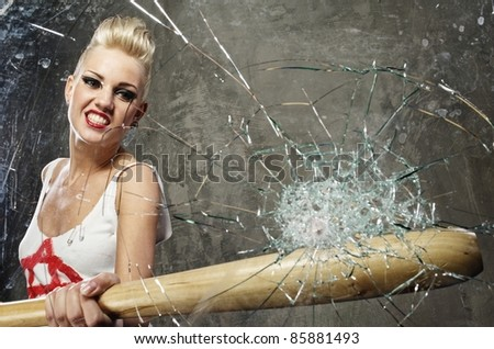 Punk girl breaking glass with a bat - stock photo