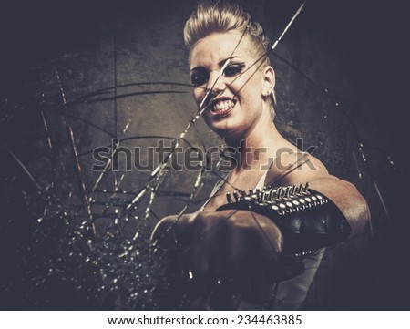 Punk girl breaking glass with a brass knuckles  - stock photo