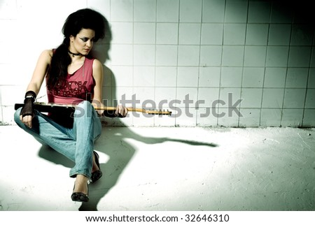 """Punk Girl playing guitar on an """"underground"""" background high contrast - stock photo"""