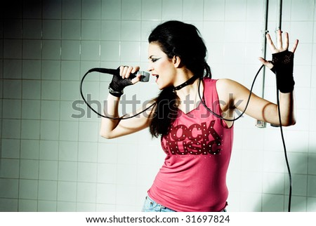 """Punk Girl singing on an """"underground"""" background high contrast - stock photo"""
