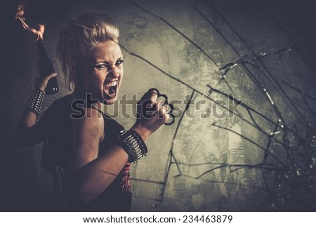 Punk girl with brass knuckles and Molotov cocktail  - stock photo