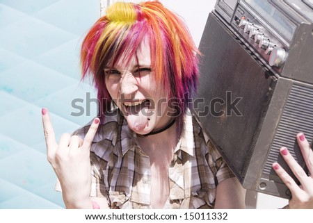 Punk girl with brightly colored hair sitting on trailer step holding boom box