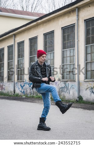 Punk guy with beanie posing in the city streets
