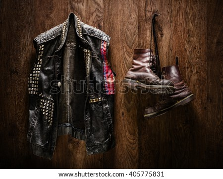 Punk-rock leather jacket and a pair of old boots hanging on a wooden wall - stock photo