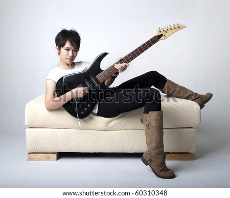 Punk Rockstar holding a guitar sitting on sofa. - stock photo