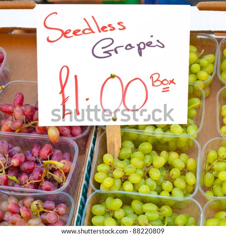 Punnets of red and white grapes for sale at a UK market stall - stock photo