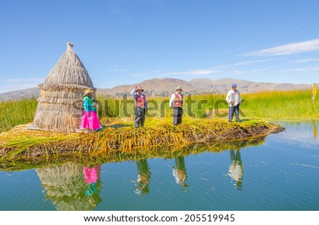 PUNO, PERU, MAY 5, 2014 - Local people in traditional attires welcome tourists coming by boats from Puno town to visit floating Uros islands on Lake Titicaca - stock photo
