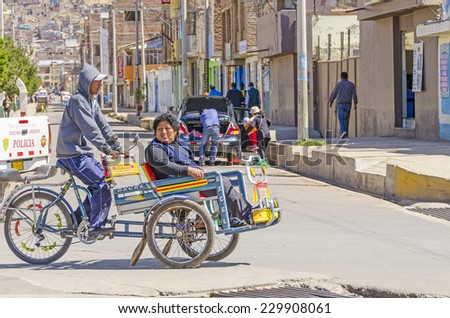 PUNO, PERU, MAY 5, 2014: Pedicab transports local woman  in city center