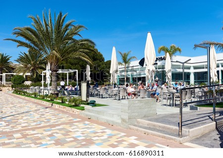 Punta Prima, Spain - March 28, 2017: Tourists sitting in a seafront cafe. Punta Prima is a popular tourist place. Province of Alicante. Southern Spain