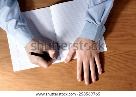 Pupil boy at a desk writing in a exercise book. Top view. - stock photo