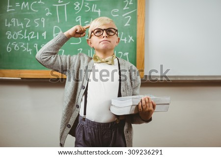 Pupil dressed up as teacher holding books in a classroom - stock photo