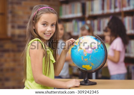 Pupil in library pointing to globe at the elementary school - stock photo