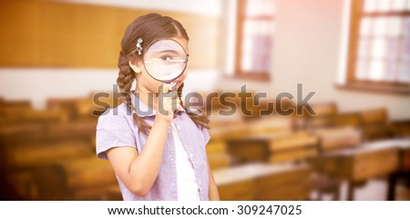 Pupil looking through magnifying glass against empty classroom - stock photo