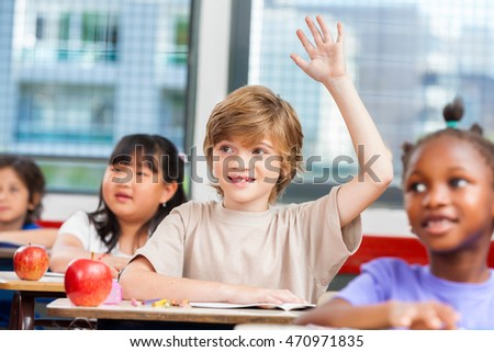 Pupil raising hand in classroom.