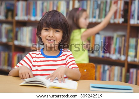 Pupil smiling at camera in library at the elementary school - stock photo