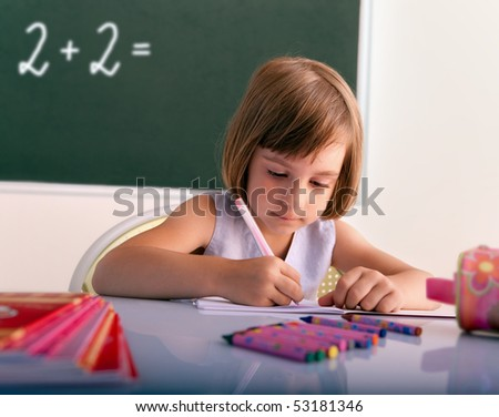 Pupil writing in a classroom - stock photo