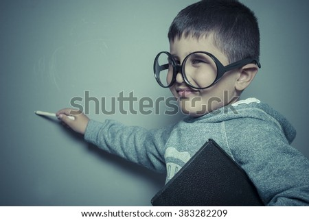 pupil, young student writing on a blackboard school with a book in hand and big glasses