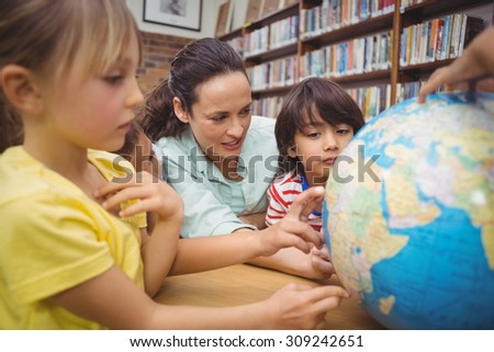 Pupils and teacher looking at globe in library at the elementary school - stock photo