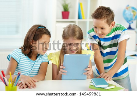 Pupils at school being interested in a new device of their friend - stock photo